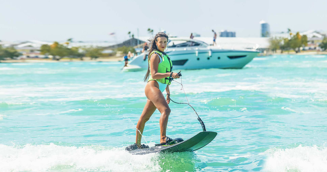 A girl poses for a photo riding her jetsurf board in Biscayne Bay.