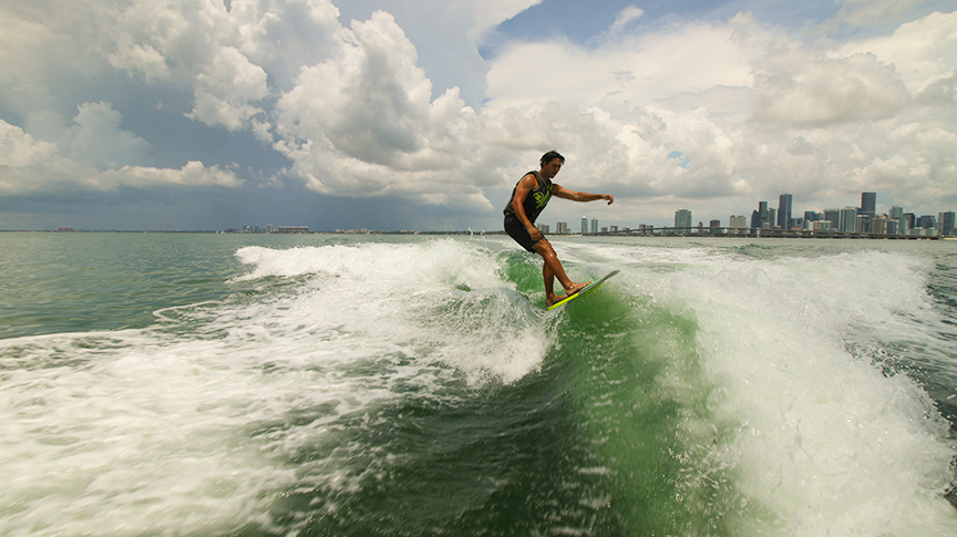 Garrison enjoy a wake surf with Downtown Miami visible in the background.